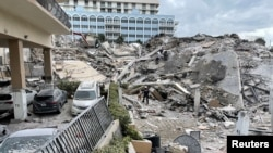 Emergency personnel work at the site of a partially collapsed building in Miami Beach, Florida, U.S., June 24, 2021.