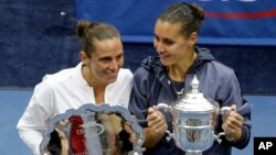 Childhood friends Flavia Pennetta, right, and Roberta Vinci pose with their awards after Pennetta won their women's championship match of the U.S. Open tennis tournament in New York, Sept. 12, 2015.