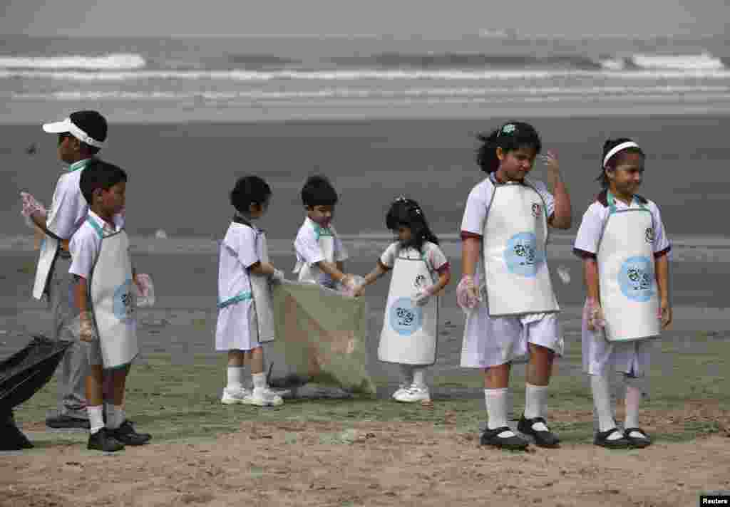 School children collect rubbish from Karachi's Clifton beach early morning April 22, 2013, during a cleaning campaign as part of the commemoration of Earth Day.