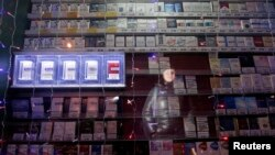 Woman is reflected in a window displaying packs of cigarettes on a street in Russia's Siberian city of Krasnoyarsk, Jan. 24, 2013.