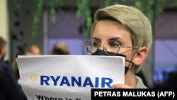 """Uma mulher com um cartaz que diz """"Onde está Roman (Protasevich)?!"""" à chegada de avião da Ryanair"""