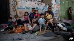 Keluarga Palestina di Gaza berada di alam terbuka dini hari, setelah rumah mereka hancur terkena serangan udara Israel (17/5).