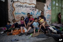 A Palestinian family sits outside their home after it was hit by an early morning Israeli airstrike, in Gaza City, Monday, May 17, 2021. (AP Photo/Khalil Hamra)