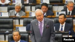 FILE - Malaysia's Prime Minister Najib Razak (R) delivers a speech next to Deputy Prime Minister Muhyiddin Yassin during a special parliamentary session convened to discuss the MH17 tragedy at the Parliament House in Kuala Lumpur.