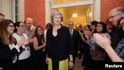 បុគ្គលិកនានាទះដៃនៅពេលដែលលោកស្រី Theresa May ដែលជានាយករដ្ឋមន្រ្តីថ្មីរបស់អង់គ្លេសដើរចូលទៅក្នុងវិមាននាយករដ្ឋមន្រ្តី 10 Downing Street នៅកណ្តាលក្រុងឡុងដ៍ ប្រទេសអង់គ្លេស កាលពីថ្ងៃទី១៣ ខែកក្កដា ឆ្នាំ២០១៦។