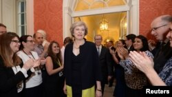 Staff members applaud as Britain's new Prime Minister Theresa May walks into 10 Downing Street after May met Queen Elizabeth in Buckingham Palace, in central London, Britain, July 13, 2016.