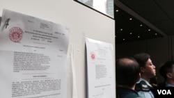 中信大廈代表星期二下午在大廈外牆張貼法庭頒發的臨時禁制令,呼籲佔領人士遵守,撤離金鐘添美道佔領區 (美國之音 湯惠芸拍攝)
