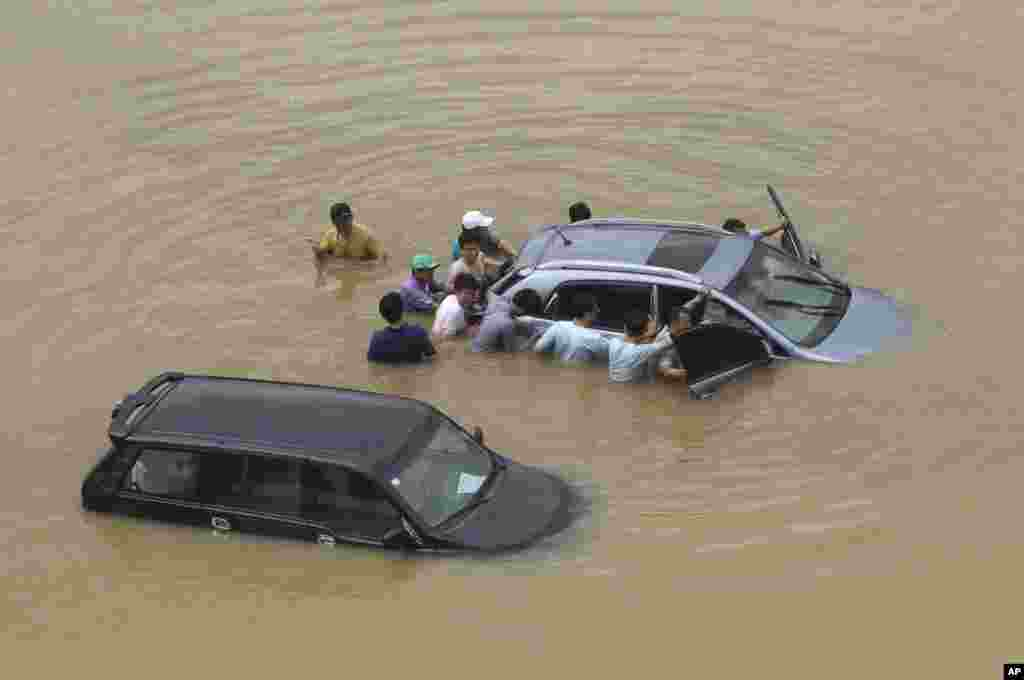 People push a vehicle submerged in flood water after a torrential rain hit the metro area in Seoul, South Korea.