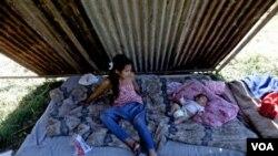 Brenda Pasan (izquierda) cuida Ludmila Romero que duerme en uno de los asentamientos ocupas en los suburbios de Buenos Aires.