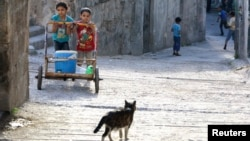 Children push a cart carrying water in the Al-Bayada neighborhood of Aleppo, Syria on April 26, 2014.