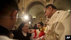 A nun takes communion from Latin Patriarch of Jerusalem Fouad Twal during Christmas midnight mass at the Church of the Nativity, traditionally believed to be the birthplace of Jesus Christ, in the West Bank town of Bethlehem early Saturday, Dec. 25, 2010.