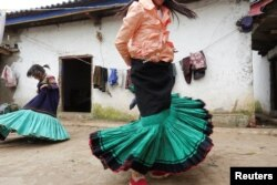 A Yi ethnic minority girl Jisi Mewuzuo (R) and her sister Jisi Meyouzuo dance holding traditional Yi skirts in Butuo County, Sichuan province, China, July 19, 2017.