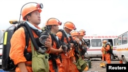 Rescuers prepare their equipment before going down a coal mine to carry out rescue operations following an explosion, in Huainan, Anhui province Aug. 19, 2014.