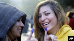 Egyptians girls show their inked fingers after casting their votes at a polling station in a referendum on a disputed constitution, Cairo, Egypt, Saturday, Dec. 15, 2012.