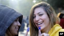 2012年12月5日两位埃及女选民在开罗的投票所投票之后展示她手指上的投票蓝印.