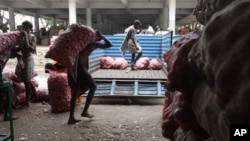 Indian laborers load bags of onions onto a truck in Hyderabad, India ( 2010 file photo)