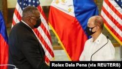 正在東南亞訪問的美國國防部長奧斯汀同菲律賓國防部長洛倫扎納舉行雙邊會談後握手。(路透社照片,2021年7月30日)
