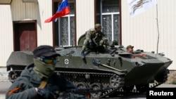 Các thành phần ly khai vũ trang và xe bọc thép treo quốc kỳ Nga lăn bánh vào thành phố Sloviansk của Ukraine, ngày 16/4/2014.