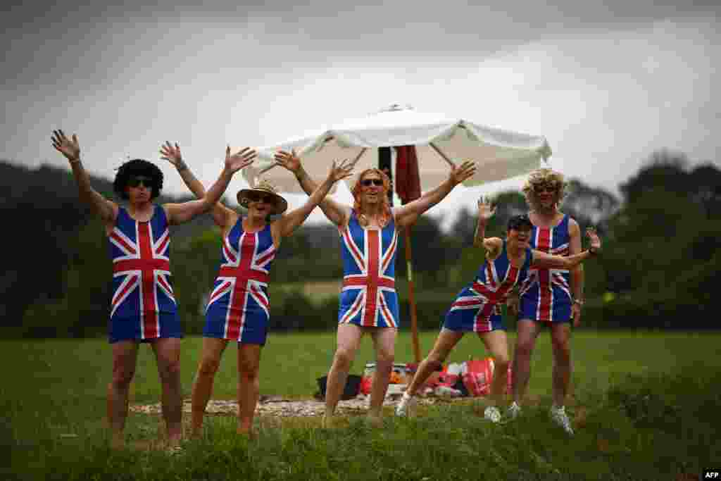 Cycling enthusiasts wearing dresses with the Union Jack gesture on the roadside as they wait for riders in Foix Prat d'Albis, France, during the fifteen stage of the 106th edition of the Tour de France cycling race between Limoux and Foix Prat d'Albis.
