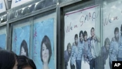Women look at the poster of the concert of the Japanese Pop group SMAP, in Shanghai. Anti-Japanese protests have already flared in numerous locations around China, and the dispute has spilled into cultural ties, 23 Sep 2010