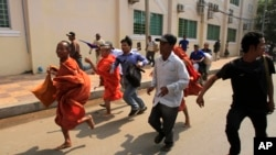 Cambodian Buddhist monks run together with supporters of Cambodian National Rescue Party from a rally site of the Democracy Square in Phnom Penh, file photo.