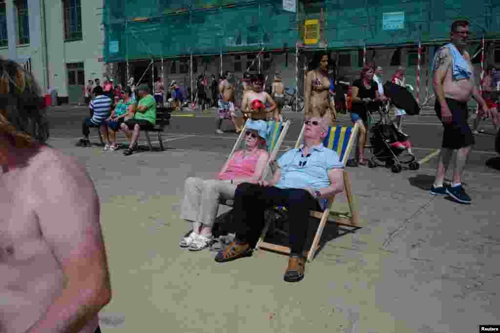 A couple sunbathe near Bournemouth beach in Bournemouth, southern England.