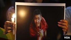 Warga Tibet di India membawa foto seorang biarawan yang tewas membakar diri, dalam aksi unjuk rasa di Bangalore (8/2).