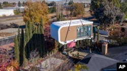 This photo provided by Mighty Buildings shows a 3D-printed house module being delivered in Livermore, Calif. Most modules are put together in a factory and then transported by truck to the owner's property. (Courtesy of Mighty Buildings via AP)
