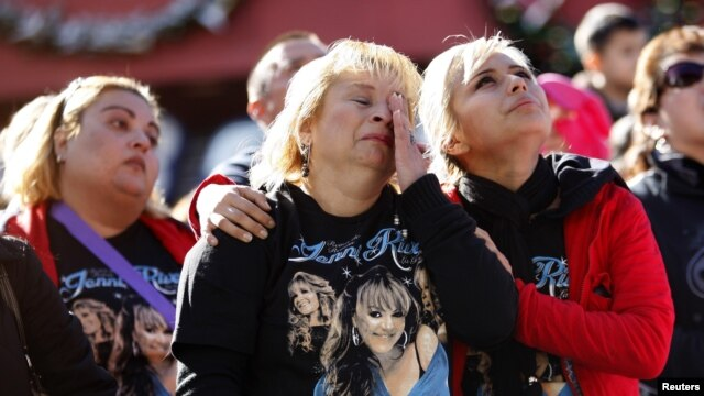 Fanáticos que no poderon ingresar al funeral observan la ceremonia a través de pantallas gigantes.