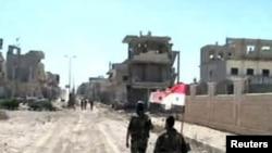 Dalam foto yang dirilis Kantor Berita Suriah (SANA) ini, nampak pasukan setia Presiden Bashar al-Assad membawa bendera nasional mereka saat melintasi jalanan di kota Qusair (5/6).