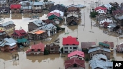 FILE - Flood-affected people row boats past partially submerged buildings in floodwaters in Srinagar, India, Sept. 9, 2014.