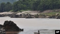 A fisherman works near the site of the proposed Xayaburi Dam in Paksey, northern Laos, file photo.