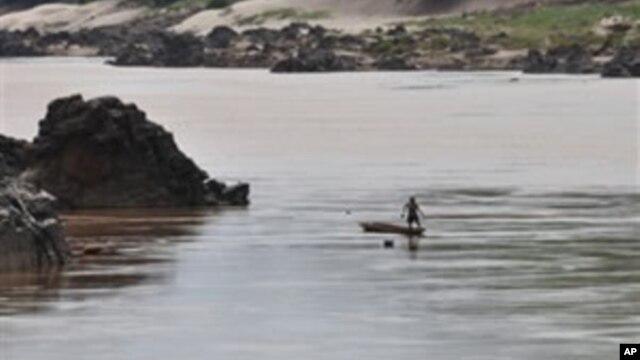 A fisherman works near the site of the proposed Xayaburi Dam in Paksey, northern Laos, file photo.