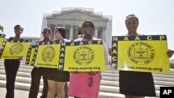 Các đại diện của quỹ Giáo dục và Bênh vực Pháp lý của Hiệp hội Quốc gia về sự Thăng tiến của những Người Da màu NAACP bên ngoài tòa nhà Tối cao Pháp viện ở Washington, 25/6/2013. (AP Photo/J. Scott Applewhite)