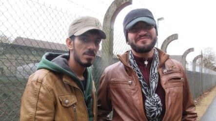 Anh Ahmad Hamdan và anh Abdulnasir Tahir đứng bên ngoài trại tị nạn ở gần Giessen, Đức.