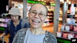 중국 인권운동가 류샤오보의 부인 류샤가 10일 핀란드 헬싱키 국제공항에 도착한 후 환하게 웃고 있다.