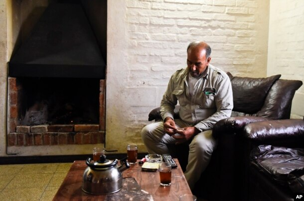 FILE - Merhi Alshebli rolls a cigarette in his living room in Juan Lacaze, Uruguay. In November 2014, locals welcomed Alshebli, his wife and their 15 children, who were fleeing Syria's civil war. The family later complained they couldn't make ends meet because of the high cost of living in Uruguay.
