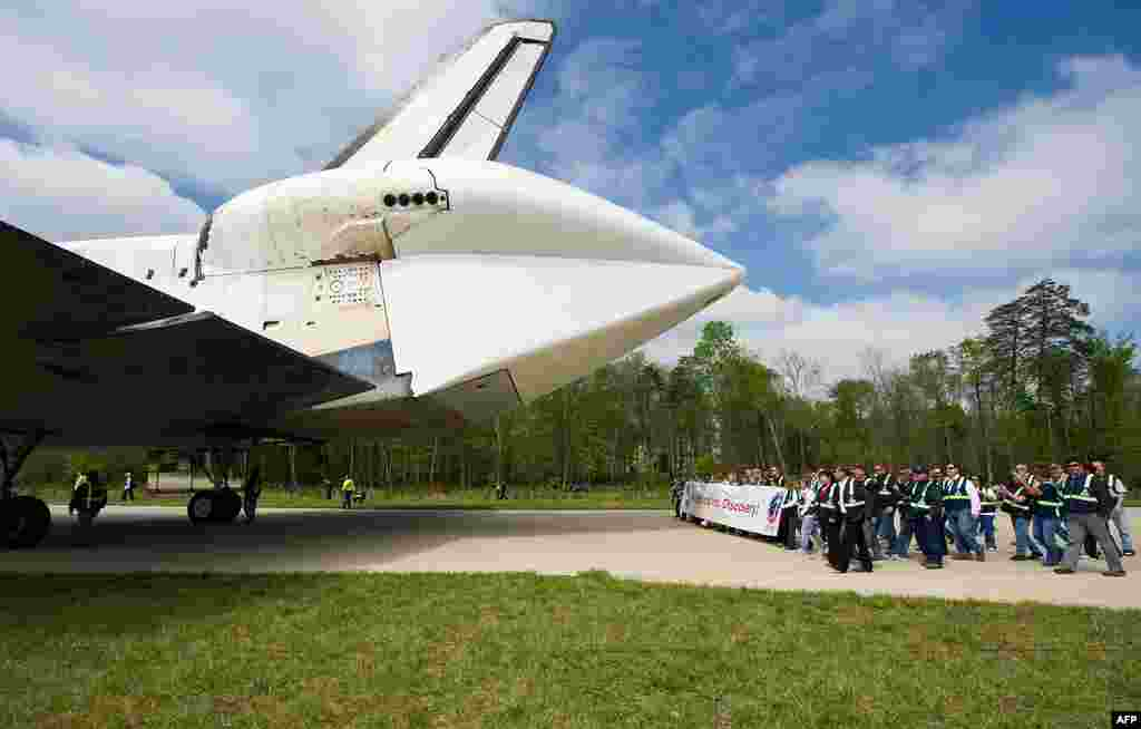 Workers from NASA Kennedy Space Center and United Space Alliance follow space shuttle Discovery as it arrives at the Steven F. Udvar-Hazy Center in Chantilly, Virginia. (NASA/Carla Cioffi)