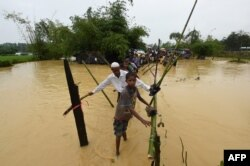 FILE - Rohingya refugees cross floodwaters at Thangkhali refugee camp in Bangladesh's Cox's Bazar district, Sept. 17, 2017.