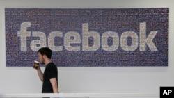 Seorang pegawai Facebook berjalan melewati logo perusahaan di markas besar Facebook di Menlo Park, California.