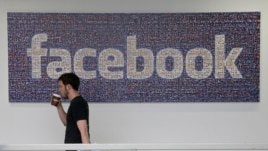FILE - A Facebook employee walks past a sign at company headquarters in Menlo Park, California.