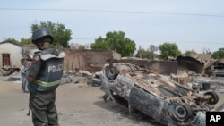 FILE - A Nigerian policeman stands guard by burned out cars and houses, following an attack by suspected Islamic extremists in Kawuri, Maiduguri, Nigeria.