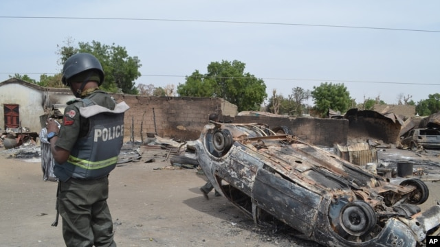FILE - Nigerian policeman guards scene of attack by suspected Islamic extremists in Kawuri, Maiduguri, in January 2014.