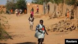 Des écoliers se hâtent de rentrer chez eux après avoir entendu des tirs à Gao, le 21 fév. 2013.
