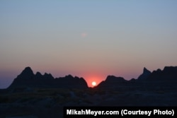 The setting sun casts a magical glow over the rocks of the Badlands.