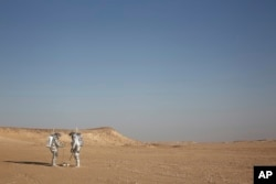 In this Feb. 7, 2018, photo, two scientists test space suits and a geo-radar for use in a future Mars mission in the Dhofar desert of southern Oman.