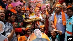 Bharatiya Janata Party supporters hold a shivling, a symbolic representation of Hindu god Shiva, and celebrate preliminary results showing a landslide BJP win in Varanasi, Uttar Pradesh, May 16, 2014.