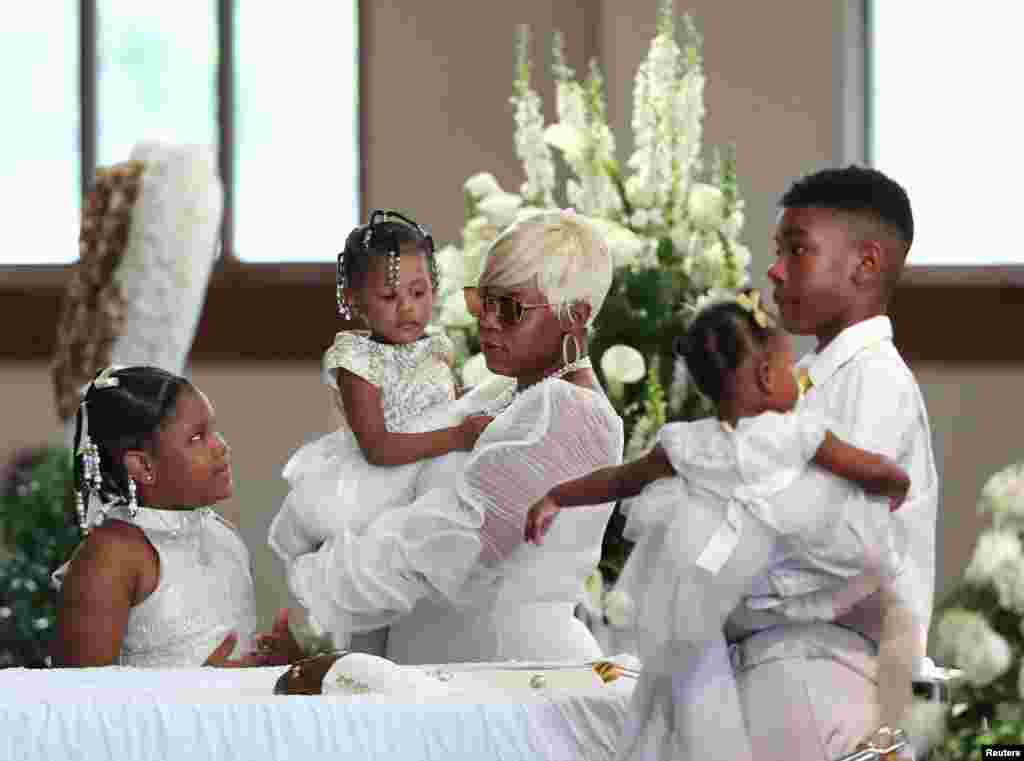 Tomika Miller, the widow of Rayshard Brooks, who was shot dead June 12 by an Atlanta police officer, holds their 2-year-old daughter Memory with her other children during his funeral at Ebenezer Baptist Church in Atlanta, Georgia.