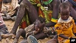 ເດັກນ້ອຍແລະແມ່ຍິງອຶດຫິວ ຈໍານວນນຶ່ງ ລໍຖ້າເອົາອາຫານຊ່ວຍເຫລືອ ຢູ່ໃກ້ໆສູນອົບພະຍົບ Kakuma ໃນເຂດເມືອງ Turkana ທາງກໍ້າຕາເວັນຕົກສຽງເໜືອຂອງນະຄອນຫລວງໄນໂຣບີ ຂອງປະເທດເຄັນຢາ, ວັນທີ 8 ສິງຫາ 2011.