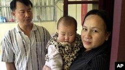 Ông Huang Chin-tsai, người Ðài Loan, 44 tuổi, và vợ Vũ Thị Minh, 30 tuổi, từ Việt Nam và cô con gái 6 tháng tuổi tại tư gia ở Vạn Lịch, 30 dặm phía bắc Đài Bắc